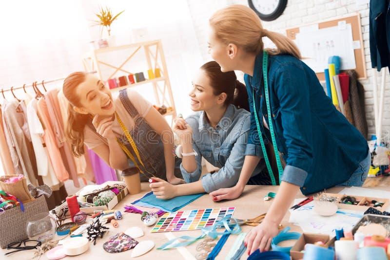 3 женщины на фабрике одежды Они выбирают поток для нового платья стоковые изображения rf