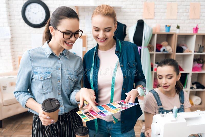 3 женщины на фабрике одежды Они смотрят картины цвета для нового платья стоковые изображения rf