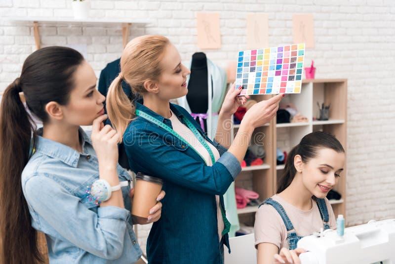 3 женщины на фабрике одежды Они смотрят картины цвета для нового платья стоковое фото