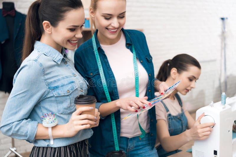 3 женщины на фабрике одежды Они смотрят картины цвета для нового платья стоковая фотография