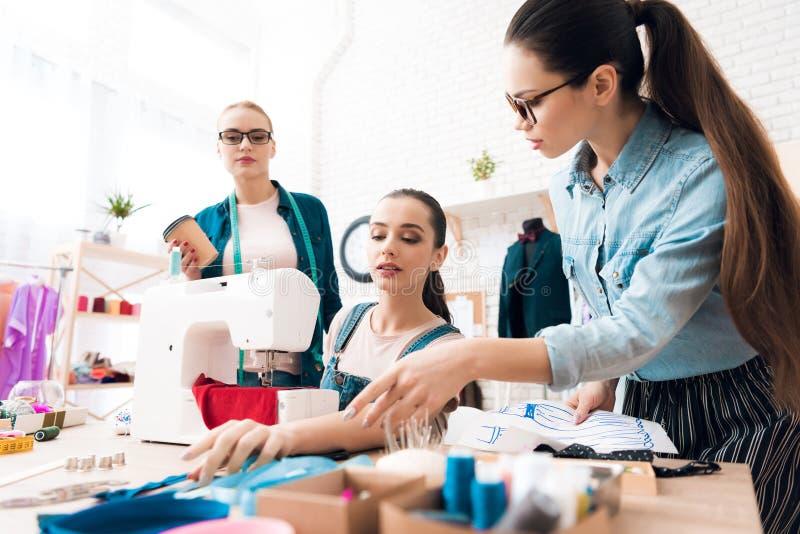 3 женщины на фабрике одежды Они смотрят светокопии стоковое фото rf