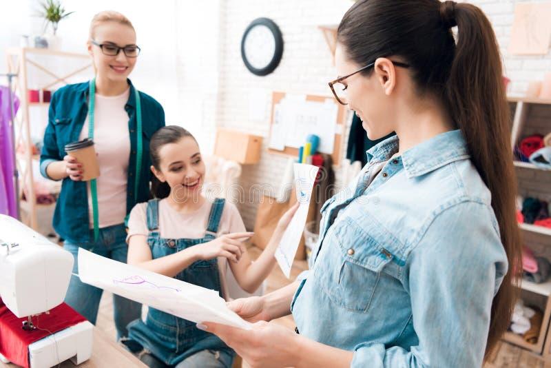 3 женщины на фабрике одежды Они смотрят светокопии стоковое изображение rf
