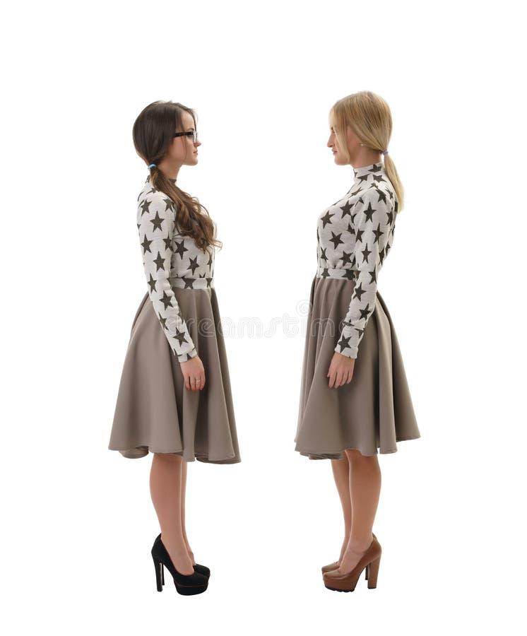 2 женщины нося такие же одежды изолированные на белизне стоковые фото