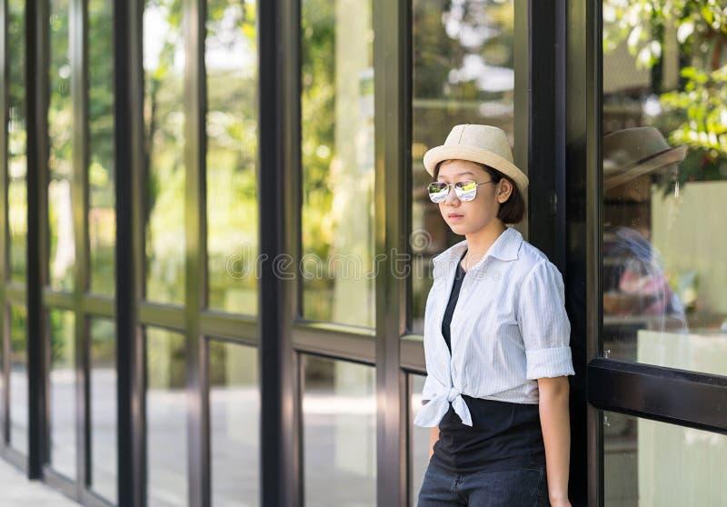 Женщины нося шляпу стоя перед стеклянным зданием стоковое изображение