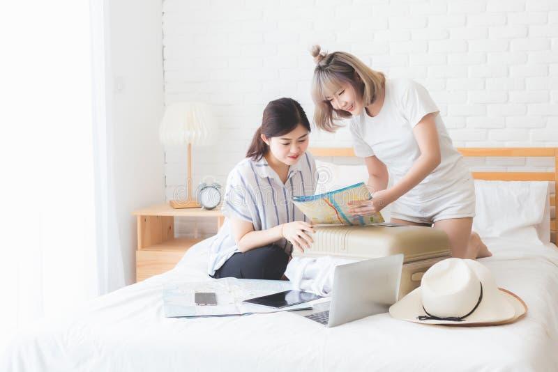 2 женщины планируют отключение и помогают подготовить багаж путешествовать за рубежом на кровати со шляпами, картами, ноутбуками  стоковые фотографии rf