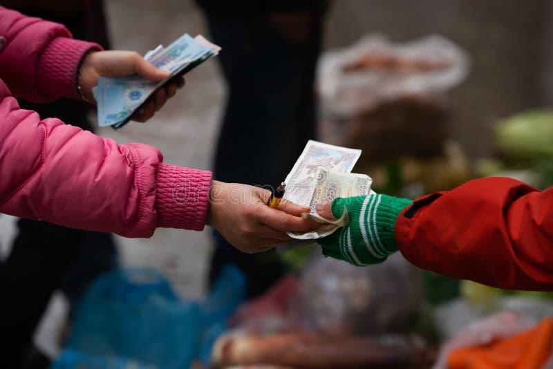 Женщины поставщика въетнамские считая въетнамский Дун в местном рынке на PA Sa, верхних достопримечательностях во Вьетнаме Мелкий стоковое изображение rf