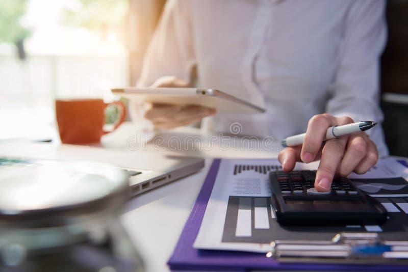 Женщины-предприниматели, работающие на портативном компьютере, с бизнес-документом, диаграммой и калькулятором на рабочем столе в стоковые фото