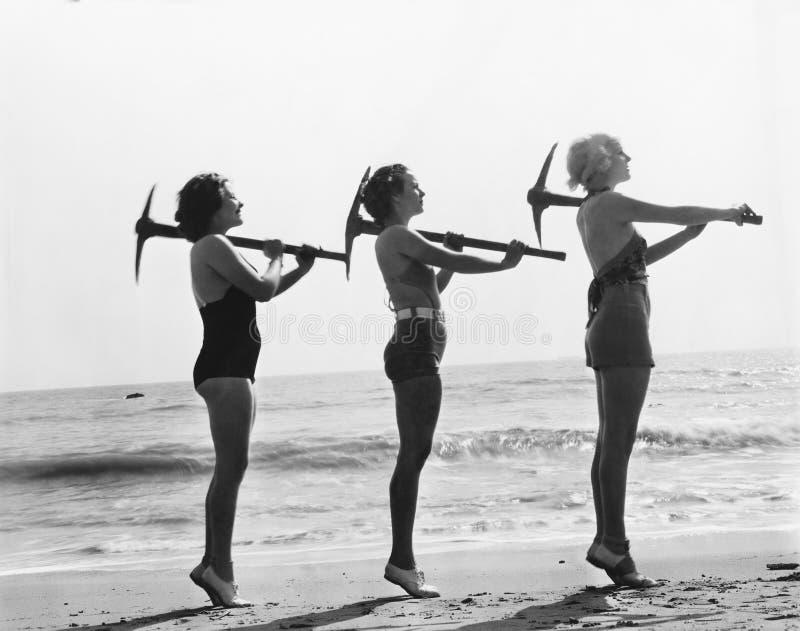 3 женщины представляя с осью выбора на пляже (все показанные люди более длинные живущие и никакое имущество не существует Предпис стоковое изображение rf