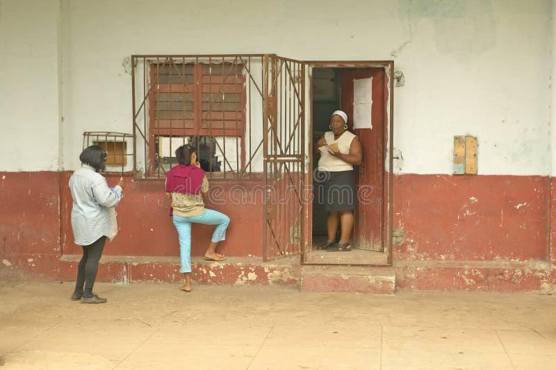 3 женщины приближают к старому зданию в деревне около El Rincon, Кубы стоковые изображения