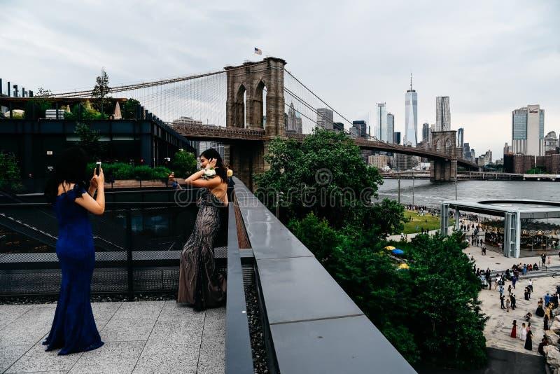 Женщины принимая фото в крыше против горизонта Нью-Йорка стоковые изображения