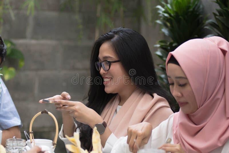 Женщины принимая фото еды на таблицу обедая во время celebr ramadan стоковое изображение