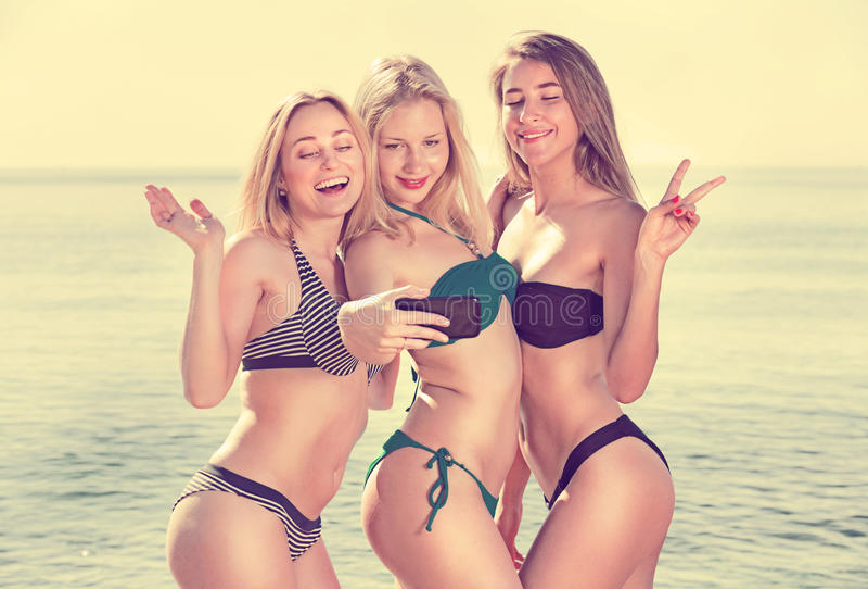 Женщины принимая фото собственной личности на пляже стоковое фото