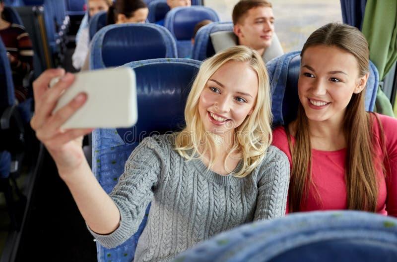 Женщины принимая selfie smartphone в шине перемещения стоковые изображения rf