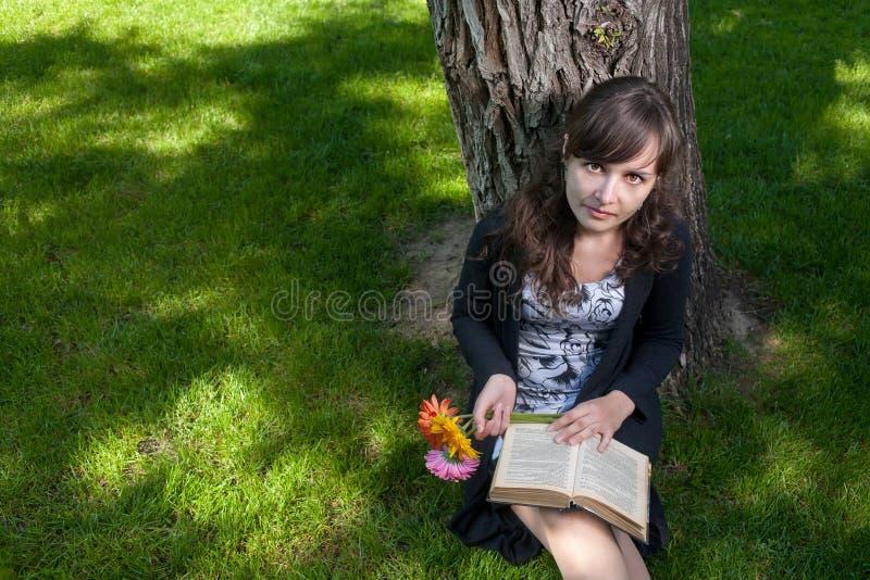 Женщины при цветки и старая книга сидя около дерева стоковое изображение