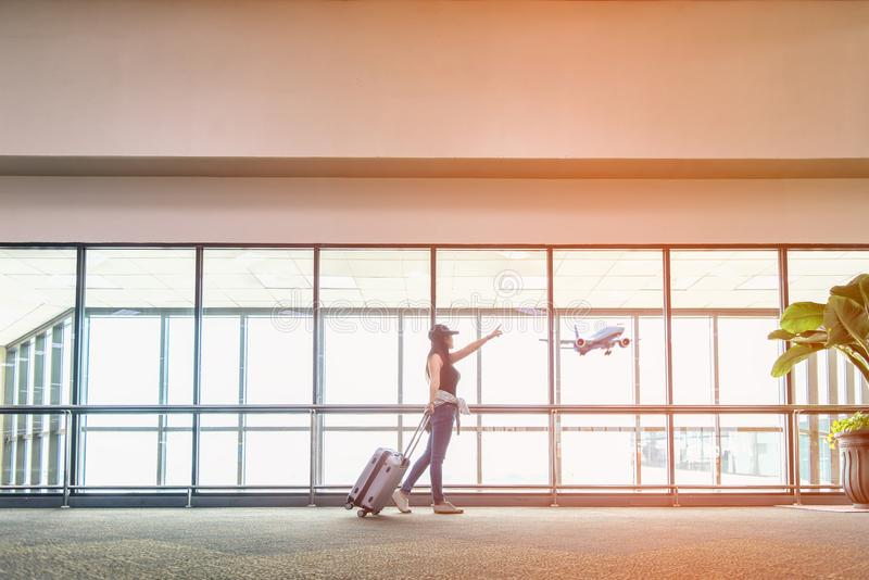 Женщины путешественника планируют и рюкзак видит самолет на окне авиапорта стеклянном, сумке владением девушки туристской и ждать стоковое изображение rf