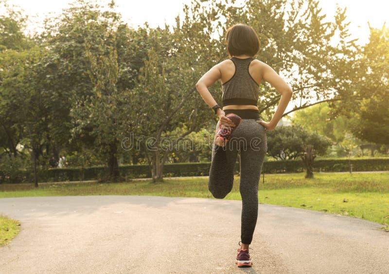 Женщины работать протягивает ее ногу ослабляют для того чтобы muscle для бежать стоковое изображение