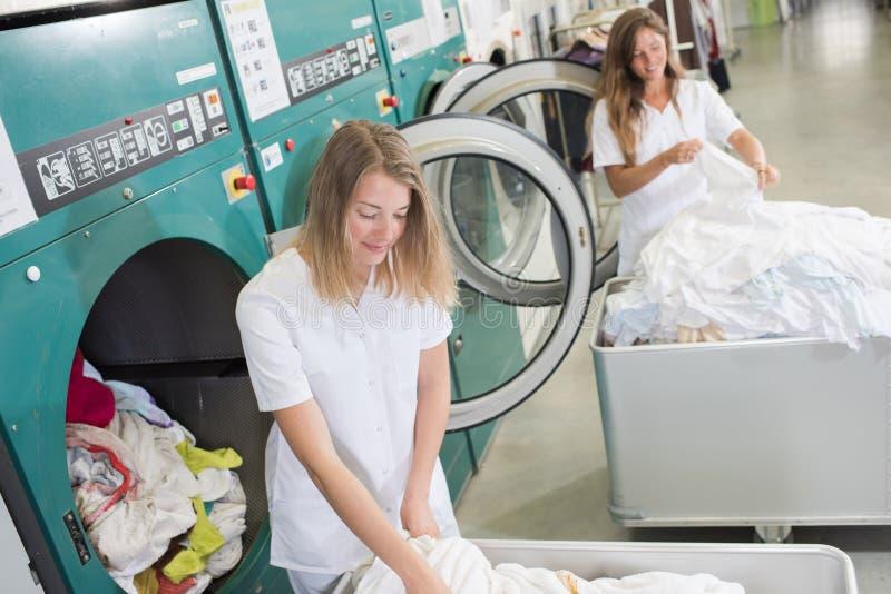 Женщины работая на промышленной прачечной стоковое изображение