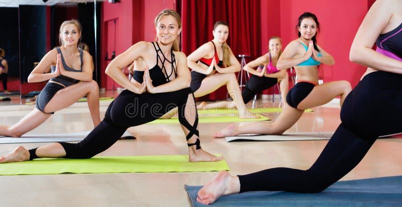 Женщины работая представления йоги в фитнес-центр стоковые фото