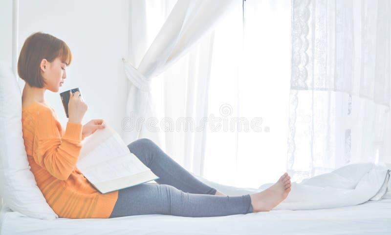 Женщины сидя книги чтения и выпивая кофе стоковое изображение