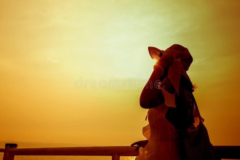 Женщины силуэта самостоятельно на заходе солнца стоковое фото rf