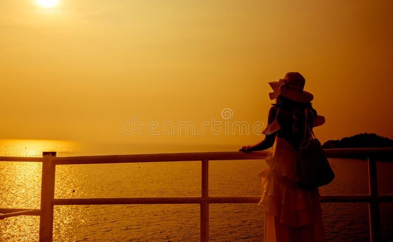 Женщины силуэта самостоятельно на заходе солнца стоковое изображение rf