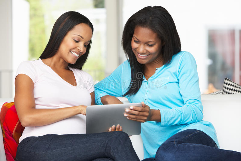 2 женщины сидя на софе с компьютером таблетки стоковое изображение rf
