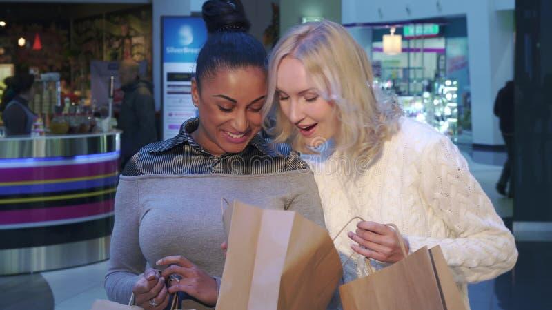 Женщины смотрят в хозяйственную сумку на моле стоковое фото rf