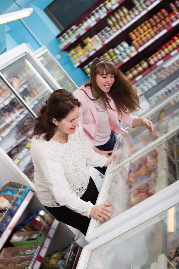 Женщины смотря в дисплее с замороженными продуктами стоковые фото