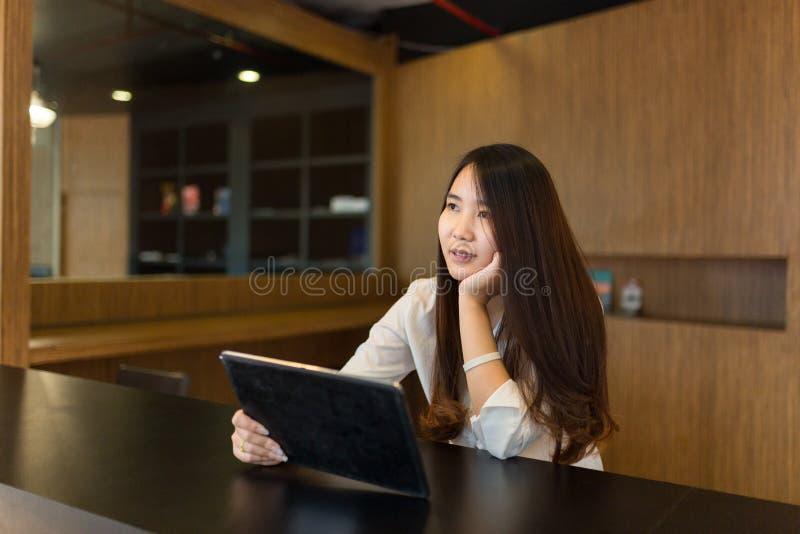 Женщины смотря в таблетке на магазине кафа стоковые фотографии rf