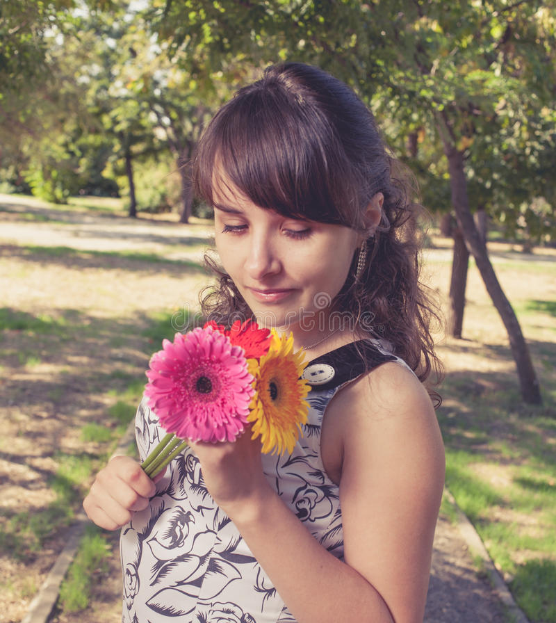 Женщины смотря цветки в ее руках стоковое фото rf
