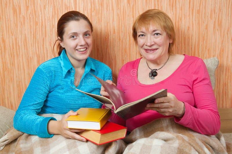 женщины софы 2 чтения книги счастливые стоковое фото