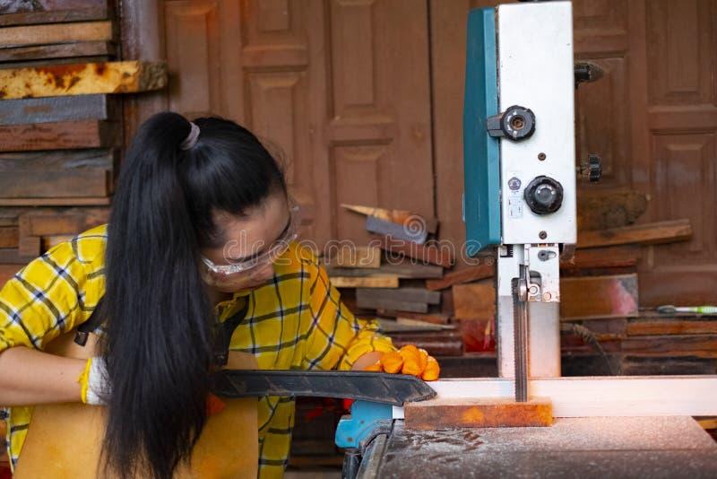 Женщины стоять ремесло работая отрезанная древесина на стенде работы с ленточнопильными станками электрические инструменты на маш стоковое изображение