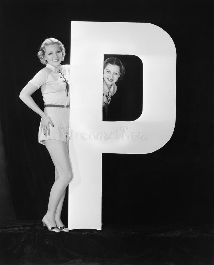 Женщины с огромным письмом p (все показанные люди более длинные живущие и никакое имущество не существует Гарантии поставщика что стоковые фотографии rf