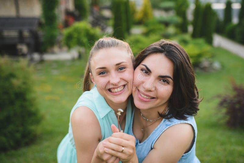 2 женщины с одуванчиком стоковое изображение rf