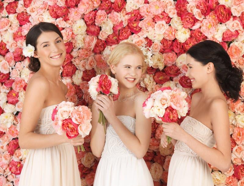 3 женщины с предпосылкой полной роз стоковое изображение