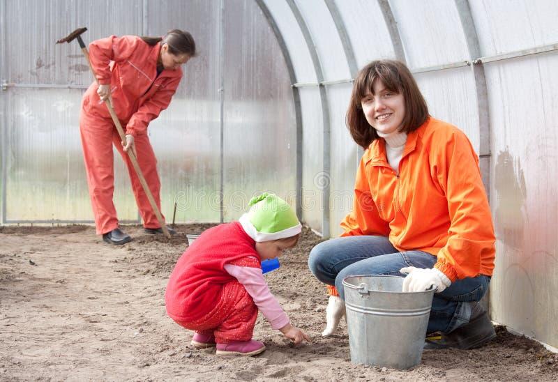 Женщины с ребенком работают на оранжерее стоковая фотография