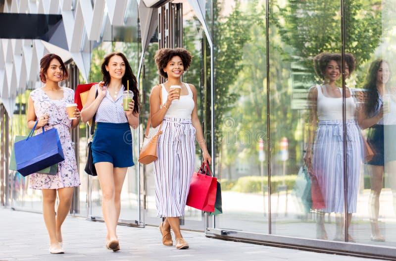 Женщины с хозяйственными сумками и напитки в городе стоковое фото