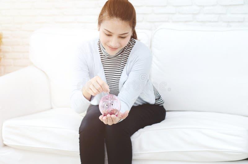 Женщины усмехаясь и розовый опарник монетки стоковая фотография rf