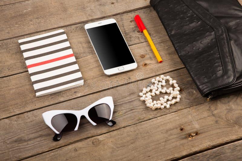женщины установили с сумкой, умным телефоном, солнечными очками, блокнотом, ручкой и жемчугом на коричневом деревянном столе стоковое фото rf