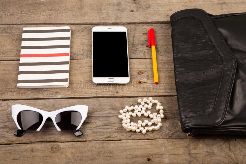 женщины установили с сумкой, умным телефоном, солнечными очками, блокнотом, ручкой и жемчугом на коричневом деревянном столе стоковое изображение