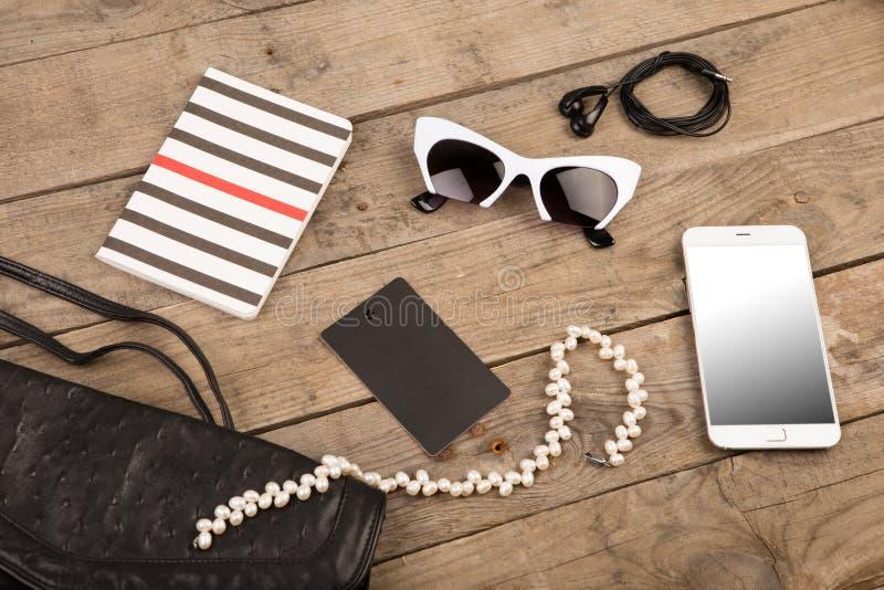 женщины установили с сумкой, умным телефоном, солнечными очками, блокнотом, наушниками, биркой и жемчугом на коричневом деревянно стоковое изображение rf