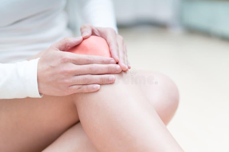 Женщины ушиба боли колена сидя и касаются ее колену концепция тягостных, здравоохранения и медицины стоковые фотографии rf