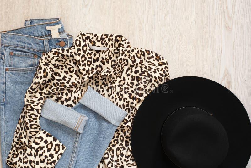 Женщины фасонируют одежды на деревянной предпосылке Плоской взгляд положения введенный в моду женщиной Рубашка, фетровая шляпа и  стоковое фото rf