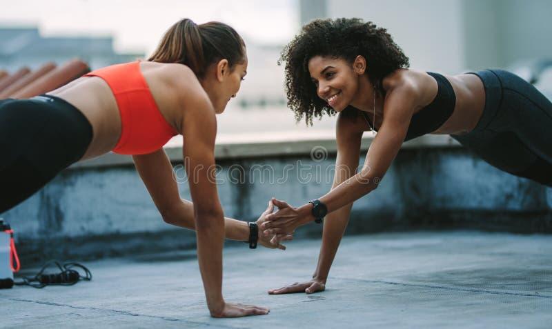 2 женщины фитнеса тренируя совместно на крыше стоковые фотографии rf