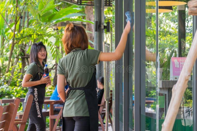 Женщины штата Азии очищая мимо wipe стекло стоковое фото