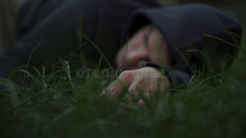 Жертва бандитов лежа на траве, укомплектовывает личным составом труп, убитый гражданина, место преступления стоковые изображения rf