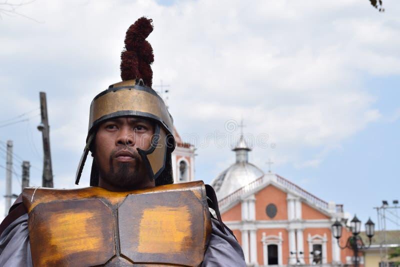 Жесткая, грубая римская драма улицы солдата, община празднует страстную пятницу представляя события это привело к распятию Je стоковые фото
