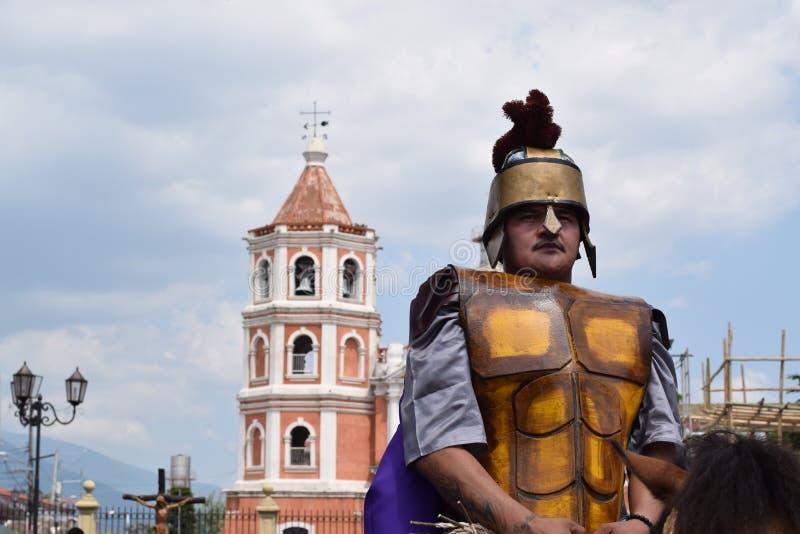 Жесткая, грубая римская драма улицы солдата, община празднует страстную пятницу представляя события это привело к распятию Je стоковое фото rf