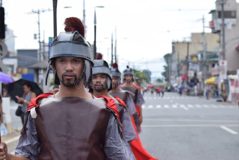Жесткая, грубая римская драма улицы солдата, община празднует страстную пятницу представляя события это привело к распятию Je стоковое изображение rf