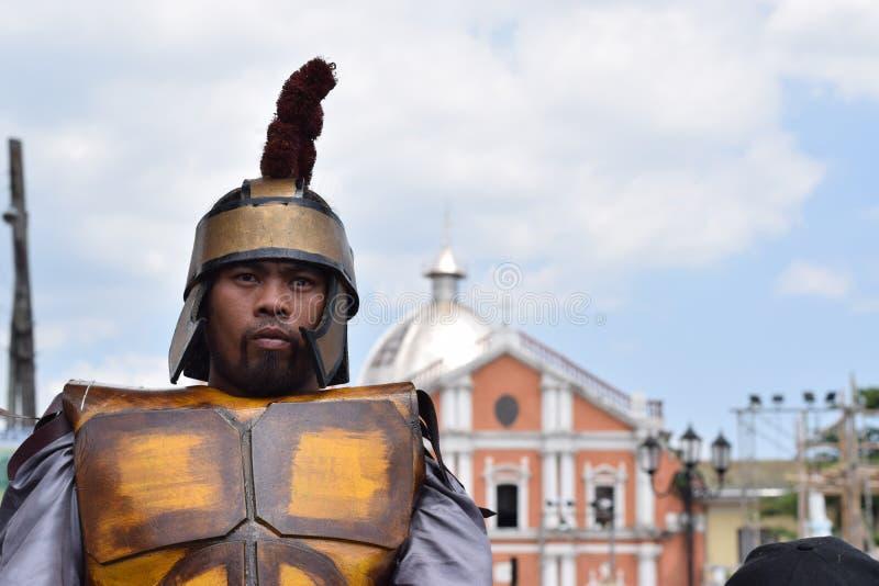 Жесткая, грубая римская драма улицы солдата, община празднует страстную пятницу представляя события это привело к распятию Je стоковые изображения rf